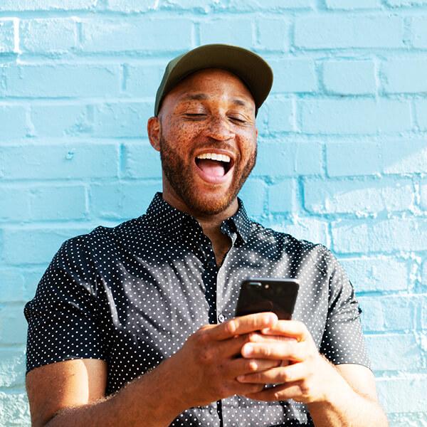 Hombre feliz mira su teléfono