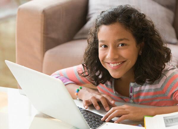 Una niña que sonríe y usa una laptop