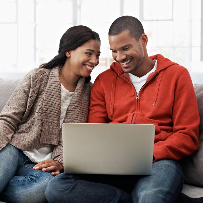 Couple looking at laptop and smiling