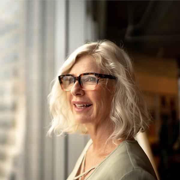 Mujer mirando hacia afuera por la ventana