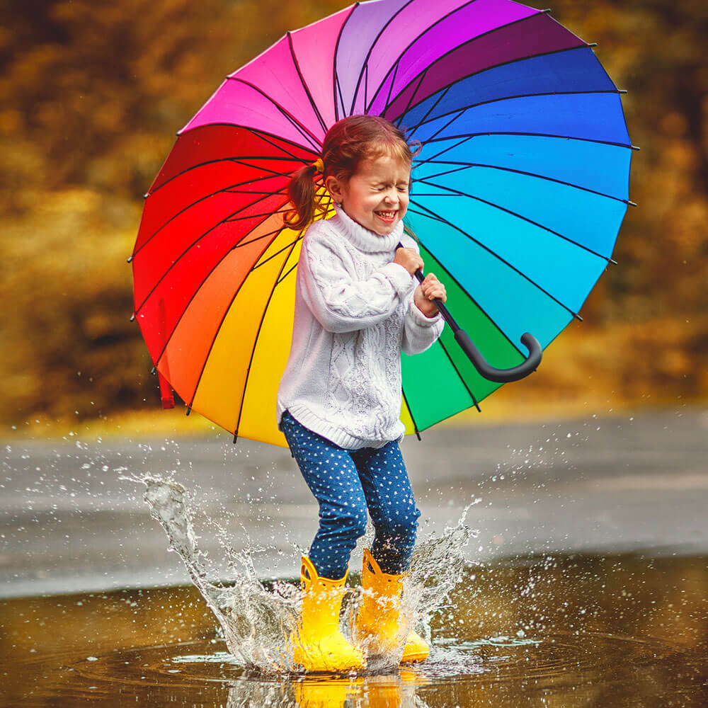 Girl with rainbow umbrella jumping in a puddle